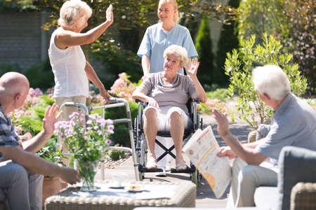 Pessoas idosas, recebendo uma mulher em uma cadeira de rodas durante a reunião no jardim em dia ensolarado Foto de archivo