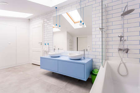 Stainless steel shower set and bathtub next to blue washbasin cabinet in bright bathroom in attic