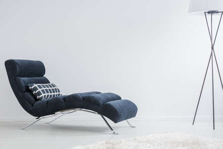 Modern metal lamp in psychologist's white room with geometric patterned pillow placed on dark settee Banque d'images