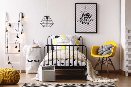 Grey pillow on yellow chair next to kids bed with beige blanket and triangle pattern pillow