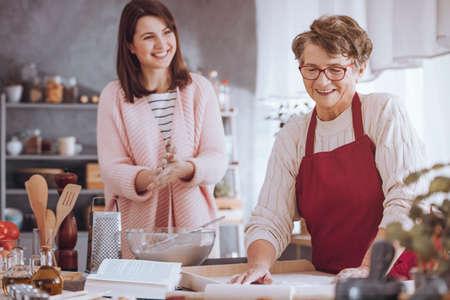 Vrij kleindochter die grootmoeder helpen terwijl samen het koken in de keuken Stockfoto - 90457116