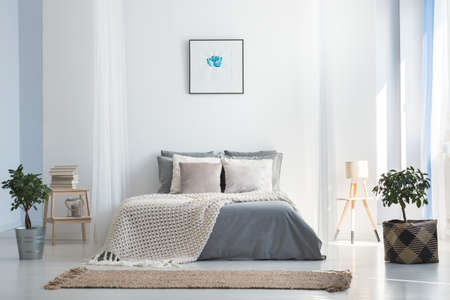 Knit blanket on king-size bed in natural warm bedroom of modern apartment in soft gray and blue colors 写真素材