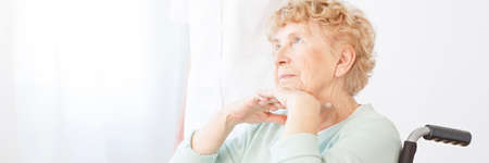 Disabled lady of old age in a wheelchair thinking about future while resting her head on her hands