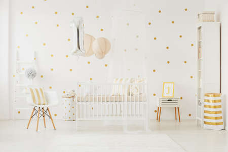 点線の壁の部屋で白いベビーベッドに固定された赤ちゃんの誕生日のヘリウムとシルバーのバルーン