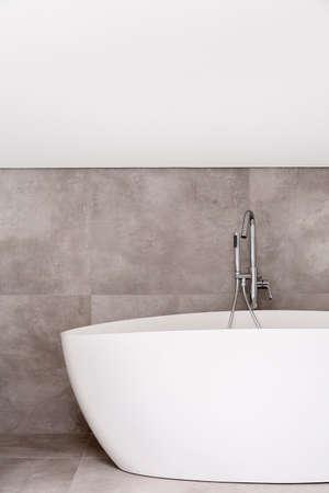 Oval bathtub with stainless steel faucet in empty bathroom with grey glaze 版權商用圖片