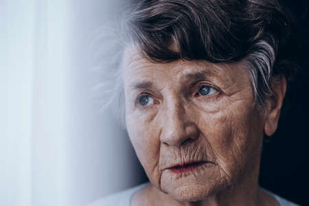 Close-up of worried, lonely old woman's face with wrinkles Stockfoto