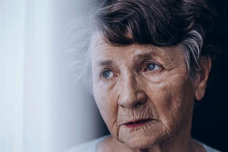 Zakończenie martwiąca się, samotna starej kobiety twarz z zmarszczeniami