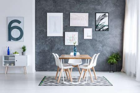 ダイニングルームの幾何学的なカーペットの上に白い椅子がある正方形のテーブルの上の青い花瓶の花