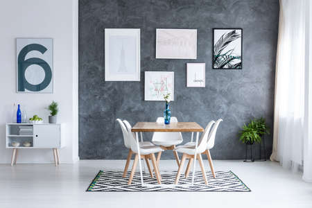 Flowers in blue vase on square table with white chairs on geometric carpet in dining room