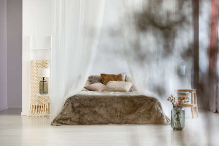 Brown pillows and fur coverlet in sophisticated interior of bohemian bedroom with canopy and ladder blanket rack Stock Photo