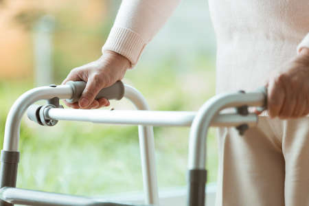 Schließen Sie oben von der älteren Person, die zu Hause einen Wanderer während der Rehabilitation verwendet