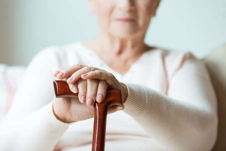 Elder holding hands on walking cane while sitting on white sofa in nursing home