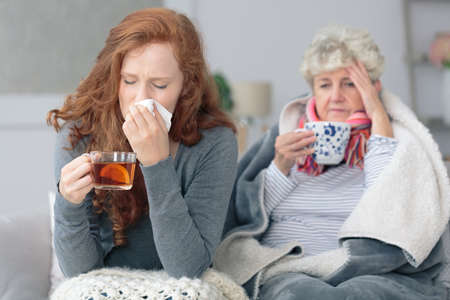 Grandmother and granddaughter sitting together with common flu during autumn weather