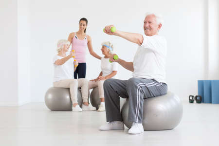 Happy elder man sitting on exercise ball and training with green dumbbells Stock Photo