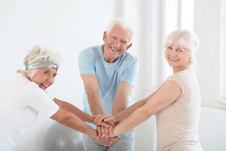 Team of happy elders with joined hands before fitness classes Banco de Imagens