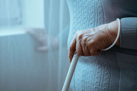 Close-up of blind person holding white cane while walking in room