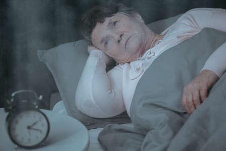 침대에 누워있는 동안 불면증으로 슬퍼하는 노인 여성 스톡 콘텐츠
