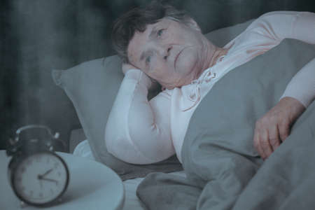 Sad elderly woman with insomnia trying to sleep while lying in bed