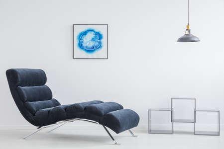 Kleine grijze lampenkap hangend boven vierkante metalen planken in witte woonkamer