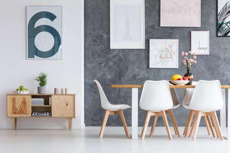 Installatie in grijze pot op uitstekende houten kast in eenvoudige eetkamer met schilderijen op muur Stockfoto