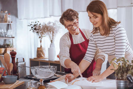 Elderly woman showing young woman how to make traditional cake