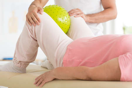 Close-up of patient holding yellow ball between her knees during rehabilitation with physiotherapist