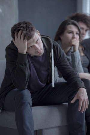 Verdrietig man denken over alcoholverslaving en wachten om een therapeut te ontmoeten Stockfoto