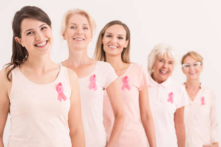 Optimistic strong women of different age groups supporting each other in a battle against breast cancer, women wearing pink ribbons
