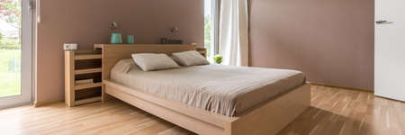 View of wooden comfortable double bed in neat master bedroom Stock Photo