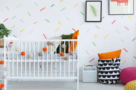 Line of colorful balls on white cradle in scandi babys bedroom with pillow in bag and pouf