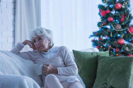Lonely senior citizen sitting on the couch during christmas