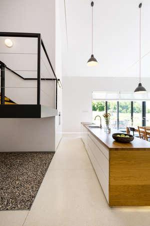流しとメザニンフロアの断片を持つ木製キッチンアイランドの眺め 写真素材