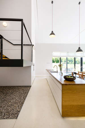 Vista dell'isola cucina in legno con lavello e frammento del piano mezzanino Archivio Fotografico - 89745405
