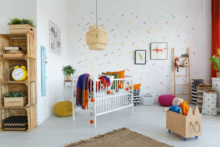 Rattan lamp above white cradle with colorful blanket in bright childs room with eco furniture
