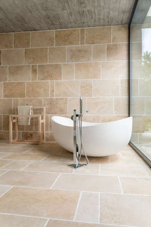 White asymmetric bath and wooden rack for towels in the photo of bright bathroom