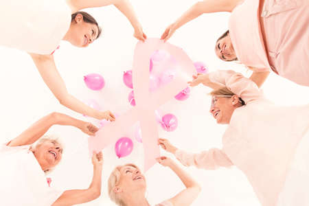 fighting cancer: Low angle of group of women holding breast cancer awareness symbol standing in circle on white background
