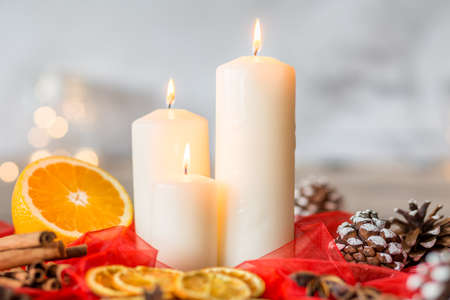 Close-up of white candles and orange on red veil with cinnamon, cones as christmas decoration