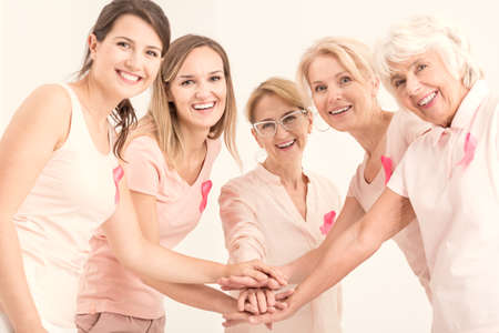 Breast cancer unity and friendship, happy women of different age groups joining hands and wearing pink ribbons Stock Photo