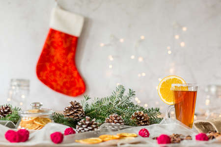 Cup of tea with lemon on christmas table with tree cones, spices and dried fruits against wall with red sock Stock Photo