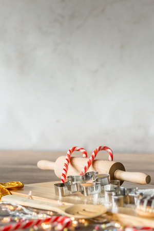 Kitchen tools, cake forms and candles on wooden board during christmas cooking