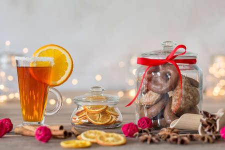 シナモン、レモン、紅茶のカップをテーブルの上の赤いリボンとガラス容器の手作りジンジャーブレッド クッキー