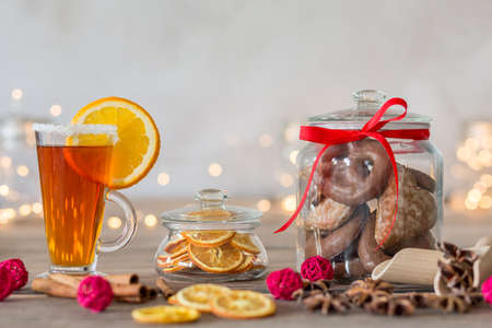 Homemade gingerbread cookies in glass container with red ribbon on a table with cinnamon, lemon and a cup of tea