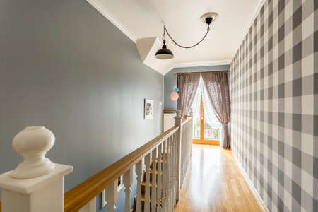 Patterned wallpaper in classic hall with lamp balustrade and curtains