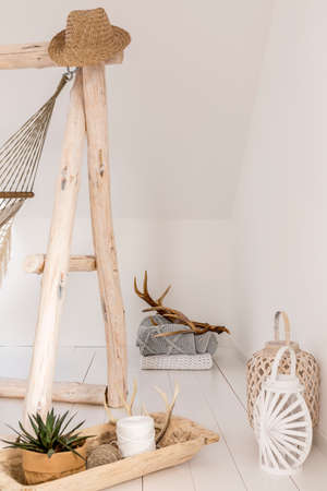 Straw hat hanging on wooden hammock frame in white room