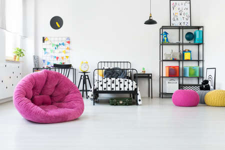Pink pouf and toys in scandi kids room with knot pillow on a bed with patterned bedsheets