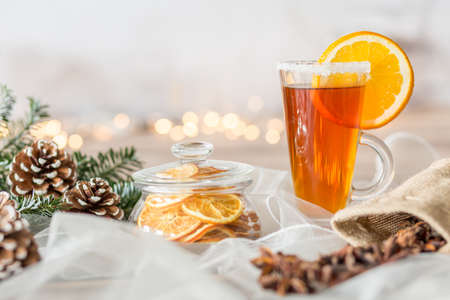 Close-up of cup of tea with lemon and lemon slices in glass container on white veil with cones Stock Photo