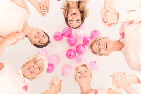 Breast cancer concept, happy women of different age groups smiling in circle holding balloons and wearing pink ribbons