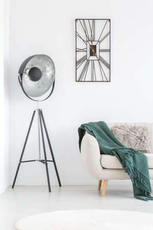 Metal lamp next to beige sofa with green blanket and grey pillow in living room with designer clock Stok Fotoğraf