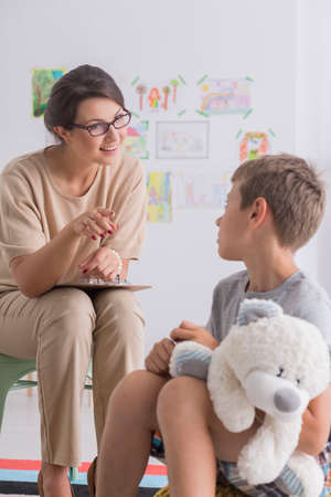 Friendly educational psychologist and little boy with autism successful therapy session