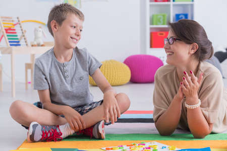 Happy little child during during therapy with school counselor, learning and having fun together sitting on the floor in a colorful playroom